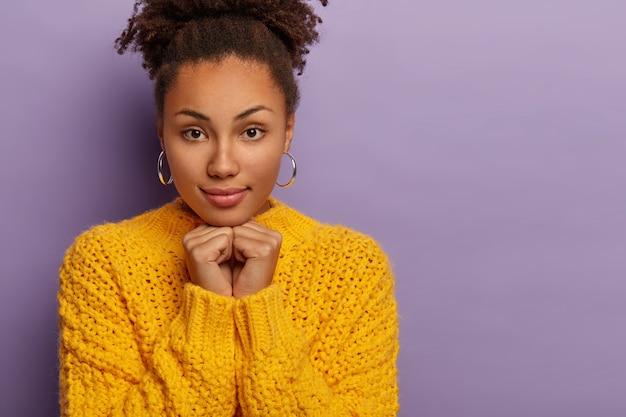 Zbliżenie dobrze wyglądającej kobiety z kręconymi włosami, która skupia się na aparacie, pewny siebie wygląd nosi żółty sweter, trzyma obie ręce pod brodą