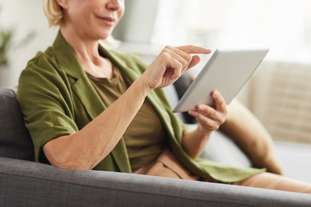 Zbliżenie: dojrzała kobieta siedzi na kanapie i pisze na cyfrowym tablecie w salonie w domu