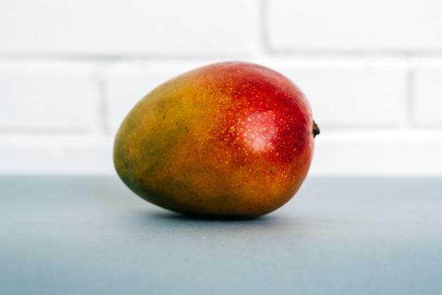 Zbliżenie dojrzałe świeże mango umieszczone na stole przed białym murem w domu