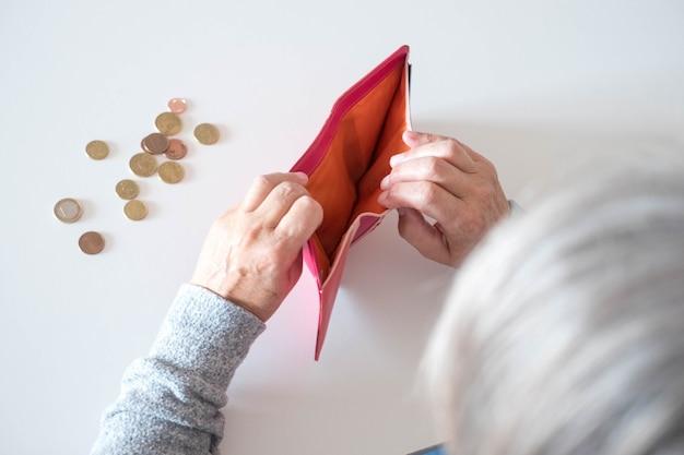 Zbliżenie dojrzałej kobiety zaglądającej do portfela bez dolara lub euro w środku - biedna emerytka z trudnym dotarciem na koniec miesiąca