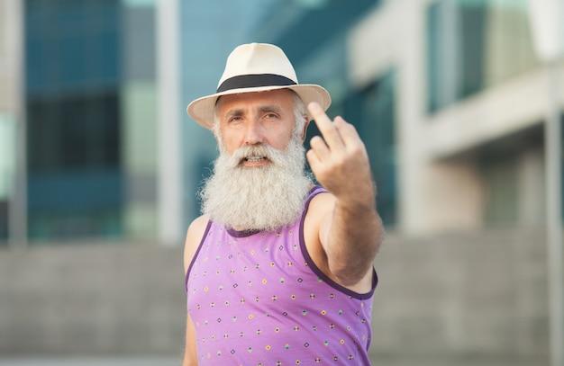 Zbliżenie dojrzały brodaty mężczyzna gestykuluje pieprzy znaka przeciw ulicznemu tłu