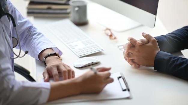 Zbliżenie doktorski dawać rada jego pacjent podczas gdy siedzący wpólnie przy doktorskim pracującym biurkiem nad uporządkowanym egzaminacyjnym izbowym diagnozy / choroby badania pojęciem.