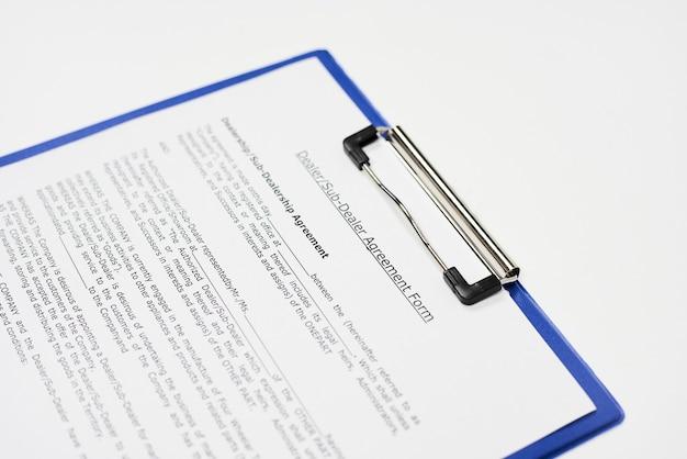 """Zbliżenie dokumentu zatytułowanego """"formularz umowy dealera i subdealera"""" na niebieskim schowku"""