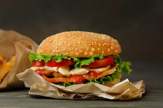 Zbliżenie domowy burger. burger z mięsem i serem. duży pyszny cheeseburger z boczkiem, serem, sałatą i pomidorem. miejsce na tekst.