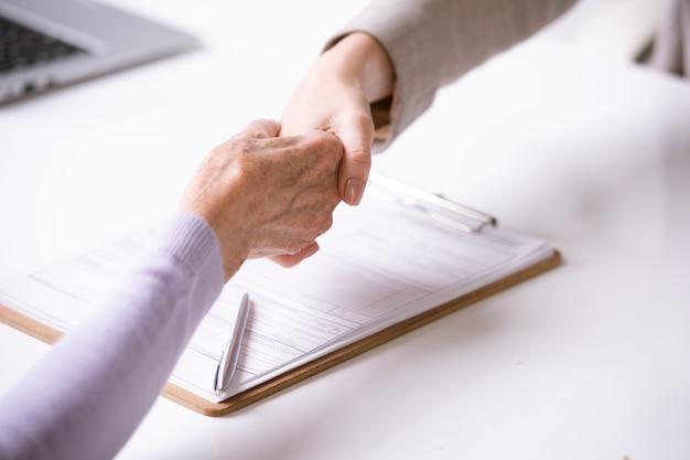 Zbliżenie doradcy co uścisk dłoni z emerytowaną kobietą po podpisaniu dokumentu