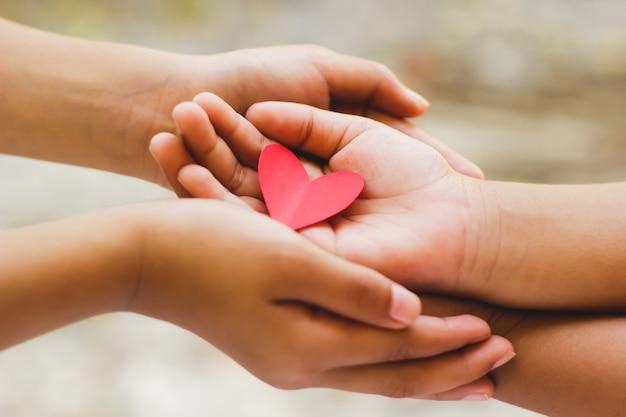 Zbliżenie dorosłych i dzieci trzymając się za ręce czerwone serce.
