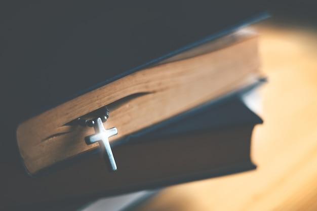 Zbliżenie drewniana chrześcijanina krzyża kolia obok świętej biblii