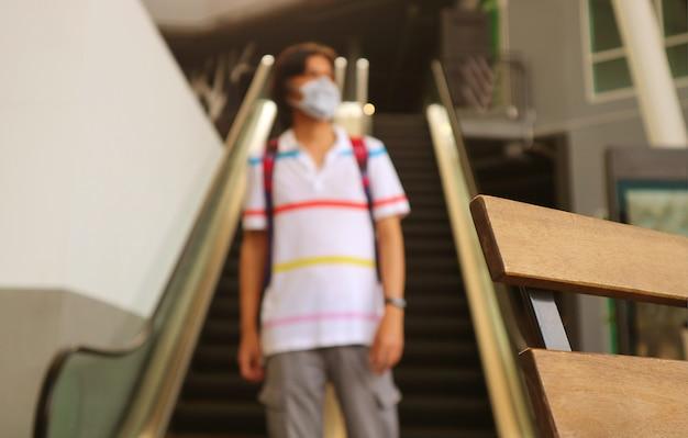 Zbliżenie drewniane krzesło z rozmytym młodym człowiekiem noszącym maskę chodzącą samotnie w nowoczesnym budynku