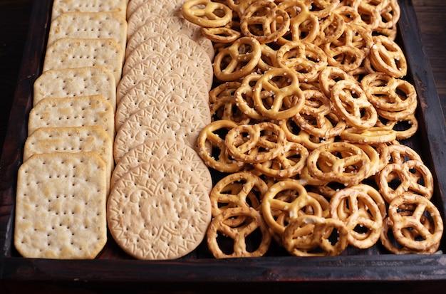 Zbliżenie drewniane pudełko z ciasteczkami, krakersami i mini precelkami solonymi, przekąskami na przyjęcia.