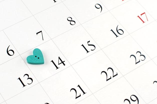 Zbliżenie drewniane serce na stronie kalendarza