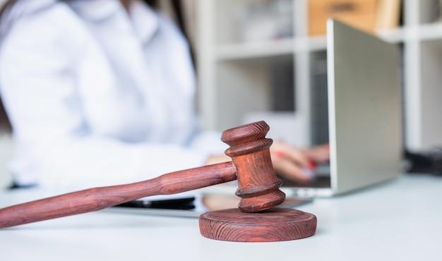 Zbliżenie drewniany młotek, prawnik pracujący na laptopie w tle, selektywne focus