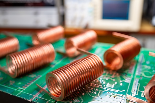 Zbliżenie drutu miedzianego wysokiej częstotliwości na zielonym mikroukładzie na tle licznych rozmytych komputerów. produkcja koncepcyjna super nowoczesnych komponentów high-tech do urządzeń nadawczo-odbiorczych