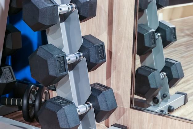 Zbliżenie dumbell na stojaku w sprawność fizyczna klubie z lustrzanym odbiciem, sprawności fizycznej pojęcie