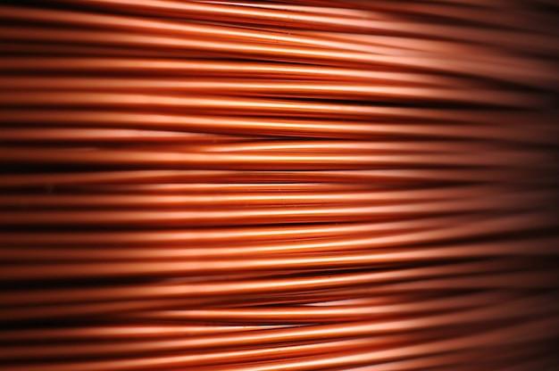 Zbliżenie dużej zwoju drutu miedzianego w produkcji części technicznych. pojęcie urządzeń elektrycznych i elektryków. przestrzeń reklamowa