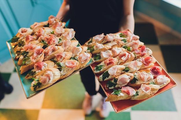 Zbliżenie duży talerz z serwowanymi kanapkami z przekąskami smażony chleb pomidorowy pietruszka i salami.