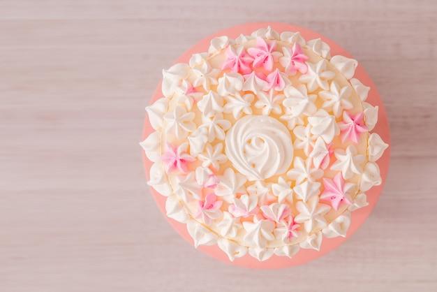 Zbliżenie: duży tort z różową śmietaną i bezą. delikatny tort urodzinowy dla dziewczynki na drewnianym tle. widok z góry.