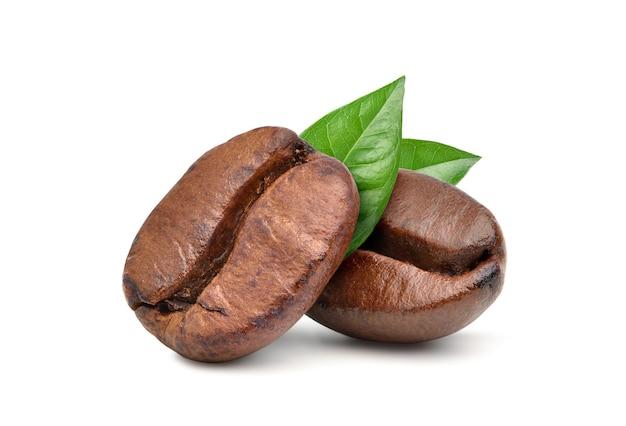 Zbliżenie dwa palone ziarna kawy z zielonymi liśćmi na białym tle