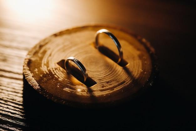 Zbliżenie: dwa złote obrączki ślubne leżące na drewnianej desce. obrączka ślubna. obrączka ślubna.