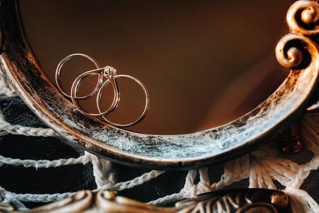 Zbliżenie: dwa złote obrączki ślubne pierścionek zaręczynowy. trzy pierścienie. obrączka ślubna. ślub.