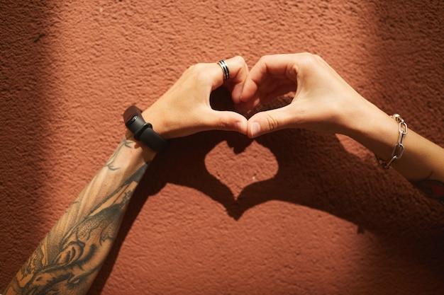 Zbliżenie: dwie dziewczyny w kształcie serca z rąk przy ścianie