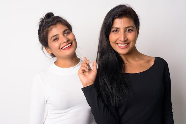 Zbliżenie dwóch młodych pięknych kobiet perskich razem jako siostry na białym tle