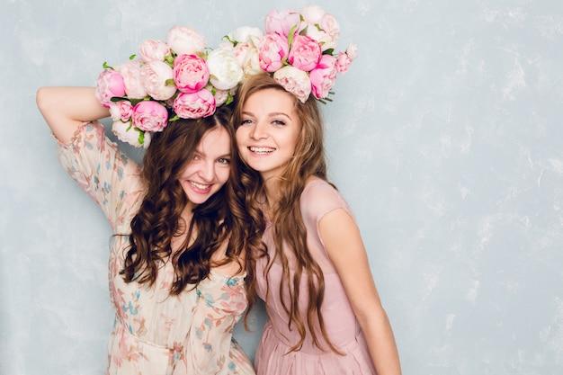 Zbliżenie dwóch pięknych dziewczyn stojących w pracowni, które bawią się głupio z diademami kwiatów na głowach.