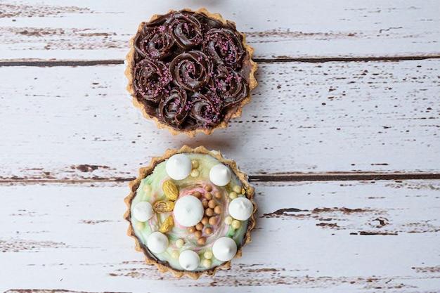 Zbliżenie dwóch placków z maślanym ciastem. posypka kremem pistacjowym i gorzka czekolada.