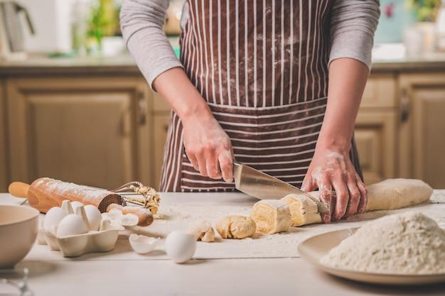 Zbliżenie dwóch rąk kobiety wyciąć ciasto nóż. kobieta w pasiastym fartuchu gotuje w kuchni