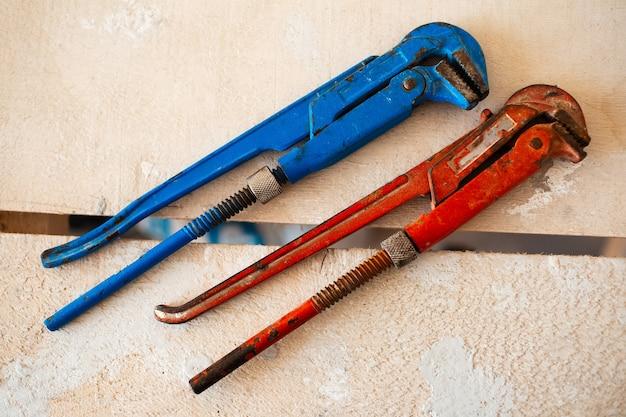 Zbliżenie dwóch regulowanych kluczy gazowych w kolorze czerwonym i niebieskim na drewnianym stole.