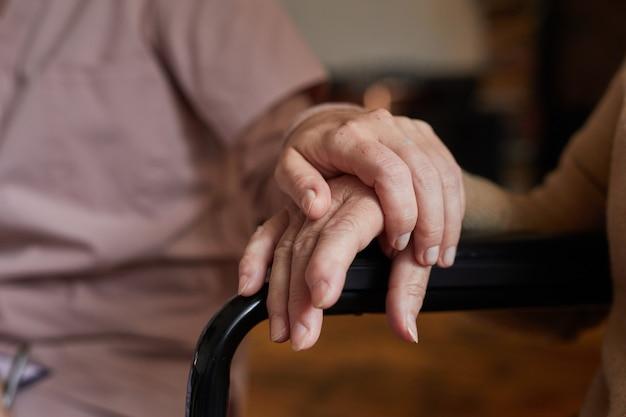 Zbliżenie dwóch starszych osób trzymających się za ręce podczas sesji terapeutycznej w domu opieki