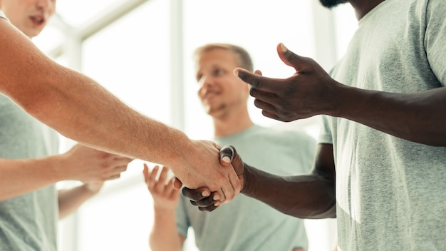 Zbliżenie dwóch towarzyszy ściskających dłonie stojących w kręgu przyjaciół
