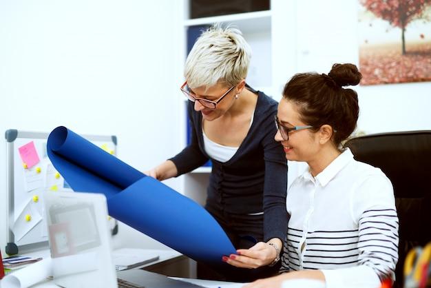 Zbliżenie dwóch uśmiechniętych skoncentrowanych stylowych kobiet w średnim wieku pracujących razem nad projektem w biurze.