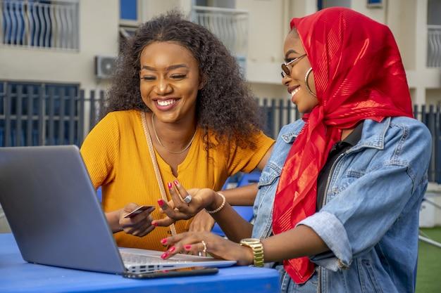 Zbliżenie dwóch wesołych młodych afrykańskich pań i laptopa