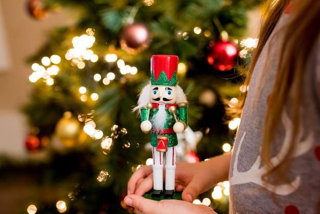 Zbliżenie dzieci dziewczyna trzyma drewnianą zabawkę dziadek do orzechów w rękach