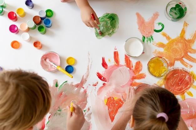 Zbliżenie dzieci malujące razem pędzlami