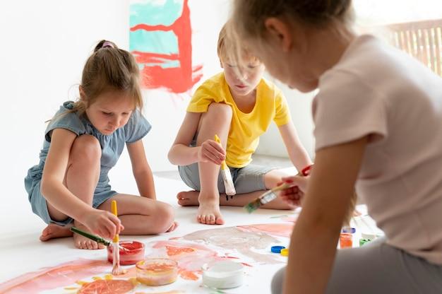 Zbliżenie dzieci malujące razem w pomieszczeniu