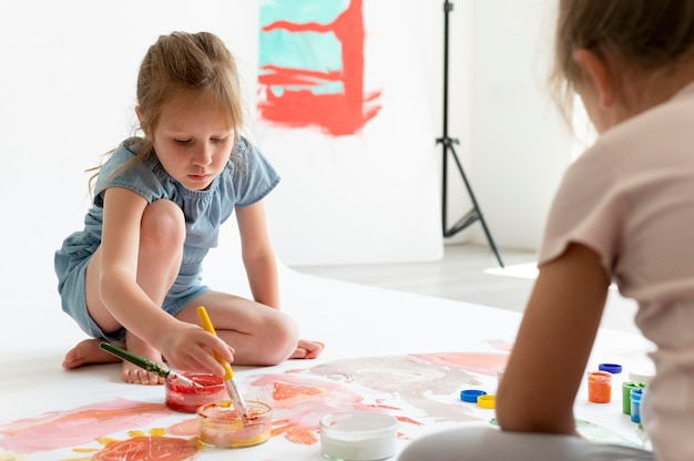 Zbliżenie dzieci malujące razem w środku