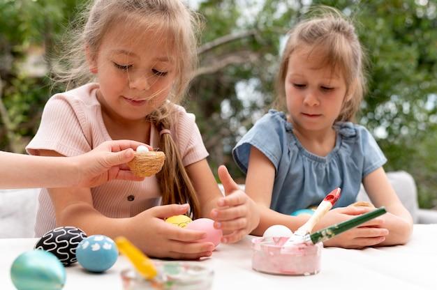 Zbliżenie dzieci z malowanymi jajkami