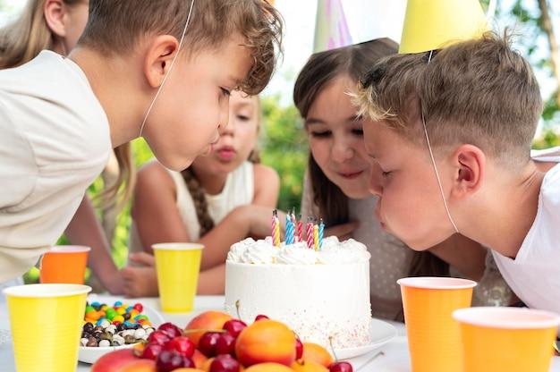 Zbliżenie dzieci zdmuchujące razem świeczki