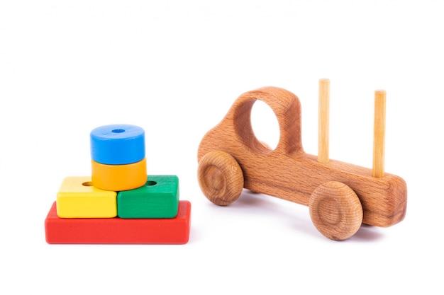 Zbliżenie dziecięca zabawka wykonana z naturalnego drewna w postaci wywrotki z drewnianymi klockami w postaci wielokolorowych geometrycznych kształtów na białym