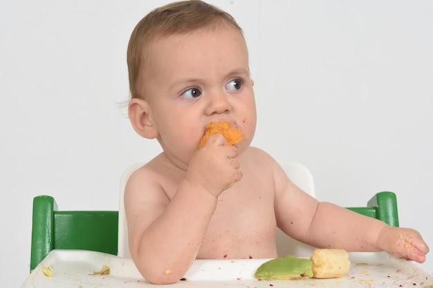 Zbliżenie dziecka je pomarańczowego owocu na białym tle