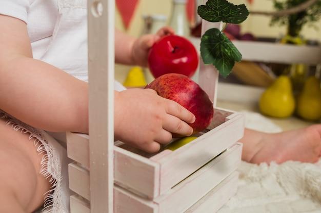 Zbliżenie: dziecko trzyma jabłka z koszem