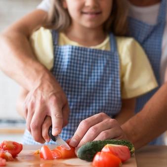 Zbliżenie dziewczyna i tata cięcia pomidora
