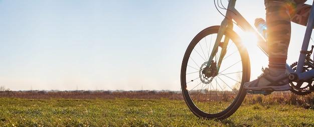 Zbliżenie: dziewczyna na rowerze, jazda na rowerze na zielonej trawie