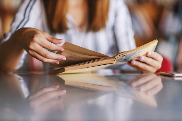 Zbliżenie dziewczyna siedzi w bibliotece i czyta książkę.