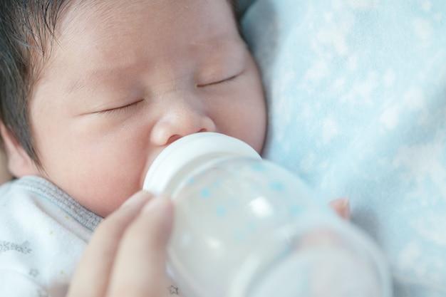 Zbliżenie dziewczynka ssie mleko matki z butelki