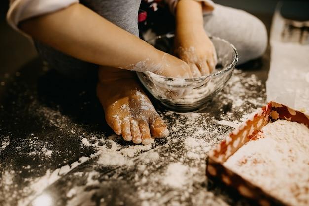 Zbliżenie dziewczyny mieszania mąki, dzięki czemu ciasto na stole w domu