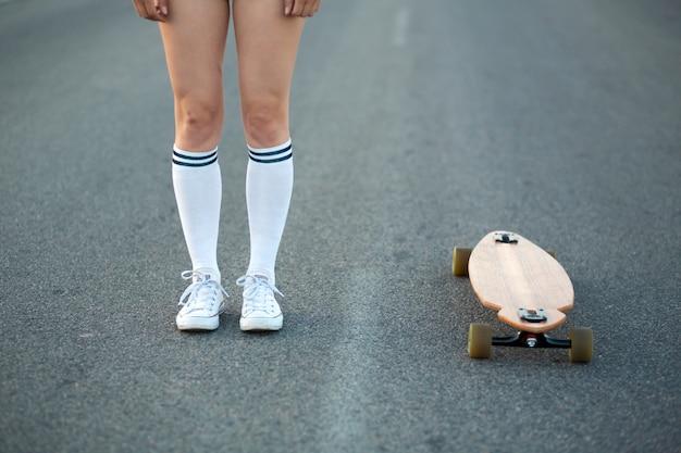 Zbliżenie dziewczyny nogi w białych pończochach zostają przy longboard na asfalcie. copyspace