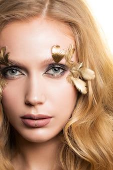 Zbliżenie dziewczyny z pięknym makijażem i złotymi piórami.