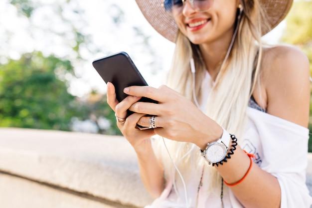 Zbliżenie dziewczyny z telefonem i słuchawkami, słuchanie muzyki i uśmiech. ładna dziewczyna trzyma swój telefon i wysyła wiadomość z ogromnymi emocjami.
